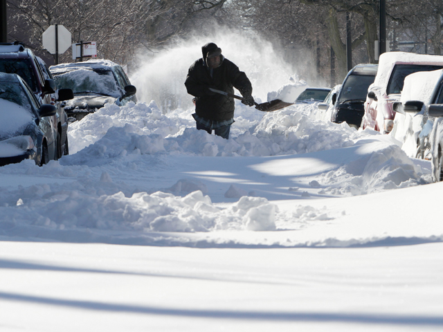 Image: Robert Brigs shovels snow at Martin Luther King Drive in Chicago