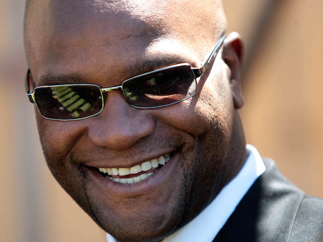 """Police Minister Nathi Mthethwa smiles while watching members of the police task force unit parachute during the launch of a new television programme """"When Duty Calls"""" which follows in the footsteps of """"Police File"""", Thursday, 8 October 2009 in Krugersdorp, west of Johannesburg.Mthethwa, his deputy Fikile Mbalula and National Police Commissioner Bheki Cele attended the launch along with the management of SABC and Primedia, The programme will broadcast information on serious incidents of crime, provide the public with feedback on police crime investigation successes as well as crime prevention hints and eliciting information from the public on wanted and missing persons. Picture: Werner Beukes/SAPA"""