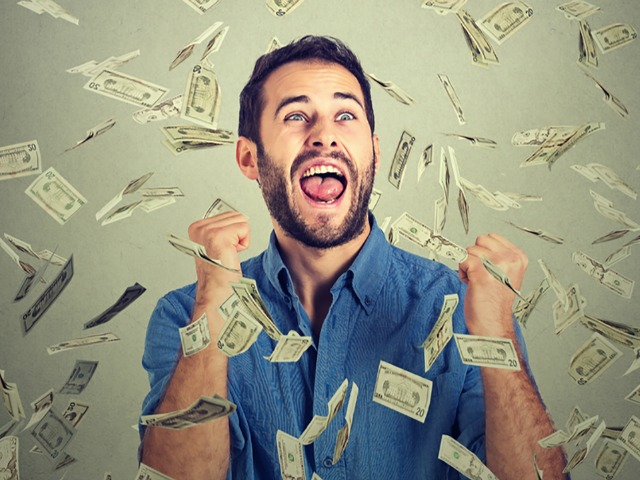 Portrait happy man exults pumping fists ecstatic celebrates success screaming under money rain falling down dollar bills banknotes isolated gray background with copy space. Financial freedom concept  ; Shutterstock ID 358763306; Cost Ctr: M770801-10942; Manager: Sandeep Dhesi; Email: sandeep.dhesi@cbc.ca; Project: Punchline