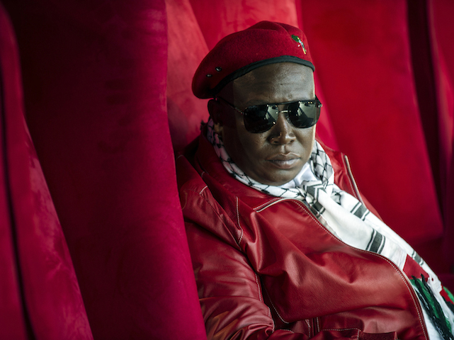 """Julius Malema, """"Commander in Chief"""" of the South African political party Economic Freedom fighters (EFF), looks on before addressing a crowd of about 3,000 EFF supporters gathered during a rally to mark the party's first anniversary in Thokoza Park in Soweto on July 26, 2014.  AFP PHOTO / MUJAHID SAFODIEN"""