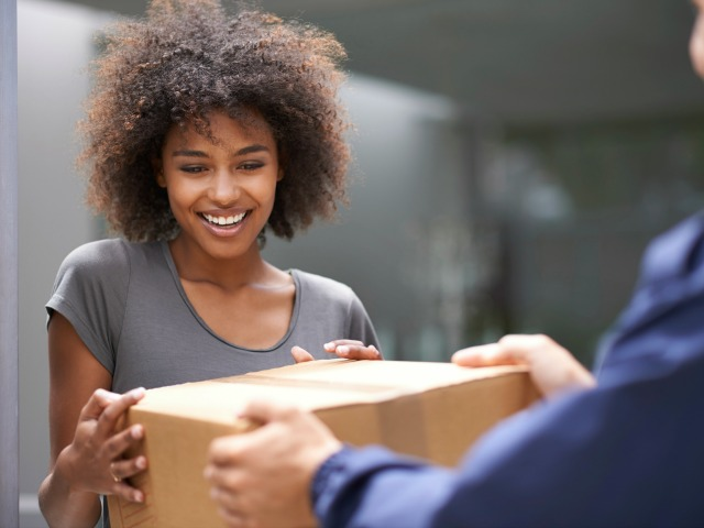 Cropped shot of a mail man handing a young woman a package