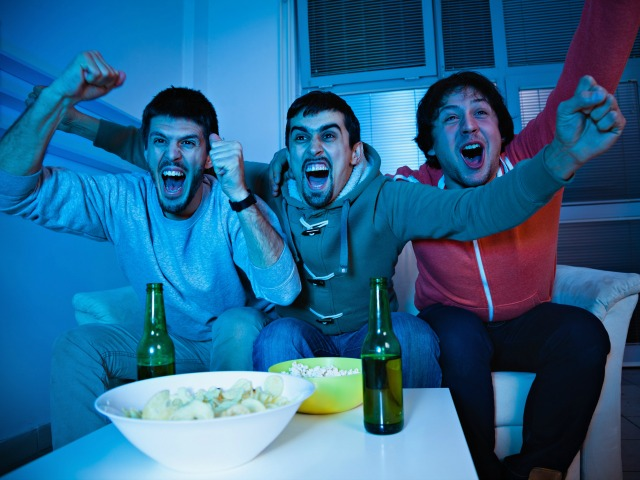 Three young men excited by goal scored during sports competition
