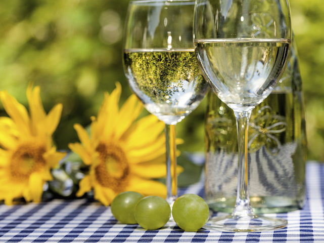 Wine glasses and sunflowers in the background