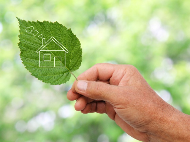 Eco house concept hand holding eco house icon in nature