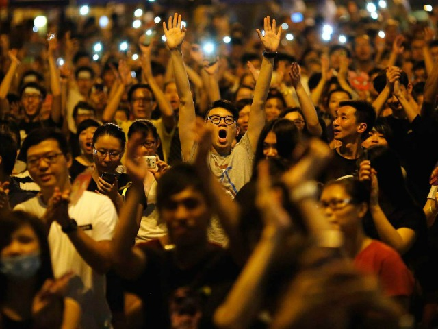 Protesters react as Joshua Wong (not pictured), leader of the student movement, speaks to the crowd outside the government headquarters building in Hong Kong October 1, 2014. Thousands of pro-democracy protesters thronged the streets of Hong Kong on Wednesday, some of them jeering National Day celebrations, and students threatened to ramp up demonstrations if the city's pro-Beijing leader did not step down. REUTERS/Carlos Barria (CHINA - Tags: POLITICS CIVIL UNREST TPX IMAGES OF THE DAY)