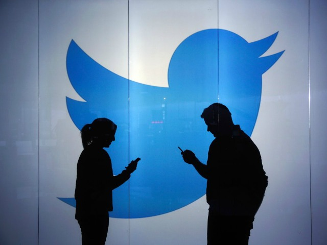 People are seen as silhouettes as they check mobile devices whilst standing against an illuminated wall bearing Twitter Inc.'s logo in this arranged photograph in London, U.K., on Tuesday, Jan. 5, 2016. Twitter Inc. may be preparing to raise its character limit for tweets to the thousands from the current 140, a person with knowledge of the matter said. Photographer: Chris Ratcliffe/Bloomberg