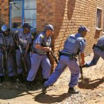 epaselect epa04707208 Police officers advance to enter mens hostels after xenophobic violence in the area overnight forced foreign shop owners to close their shops for fear of attack in Actonville, Johannesburg, South Africa, 16 April 2015. Police searched the mens hostels for weapons used by local South African men against foreign African's after five people have been killed during recent xenophobia attacks that started in the South African port city of Durban.  EPA/KIM LUDBROOK